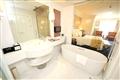 行政套房豪華衛浴內,獨立浴缸旁設置有視聽娛樂設備。