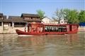 一艘遊船駛過民居群前的河道