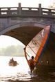風帆船愛好者正運用技巧航行過橋下